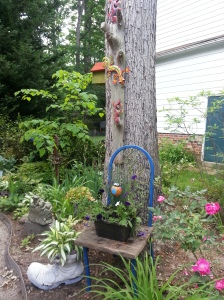 An old metal chair spray painted for the garden. I attached old barn boards for the seat and cut out the square to the hold pot. Then in the back drop a  birdhouse for my feathered visitors and lizards climbing the tree