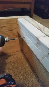 Drill a pilot hole and then screw these 2x2s at the foot and end of the mattress base so the plywood has a resting edge